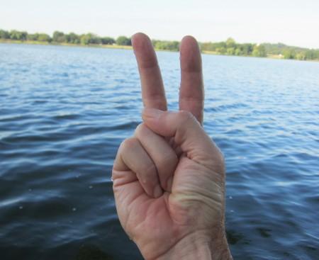 drowning persons makes palm-inward v-sign