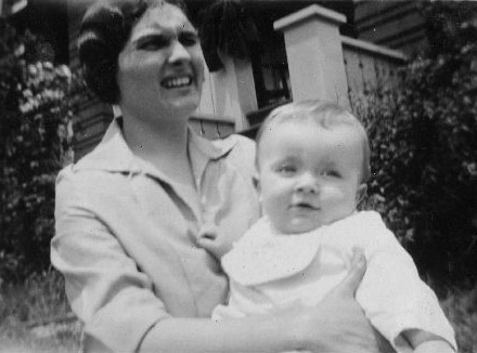 woman holding child and grimacing